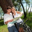 Couple on a bike ride making a stop to look at map — Stock Photo #13941788