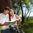 Couple on a bike ride making a stop to look at map - Foto de Stock