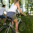 Couple riding bicycles in field by a lake — Stock Photo