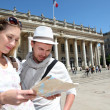 Couple holding a touristic map of Bordeaux — Stock Photo #13941850