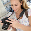 Portrait of young tourist looking at camera screen - Stock Photo