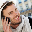 Smiling trendy guy talking on the phone in town - Stock Photo