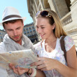 Couple of tourists looking at city tour map — Stock Photo