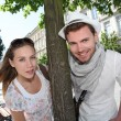 Couple standing by a tree in town — Stockfoto