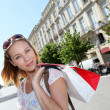 Beautiful young woman in town holding shopping bags — Stock Photo