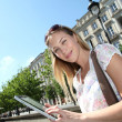 Blond woman in town using electronic tablet — Stock Photo
