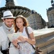 Couple standing by a fountain in Bordeaux with map — Stock Photo