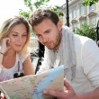 Couple sitting at a coffee shop terrace to look at map — Stock Photo