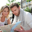 Couple sitting at a coffee shop terrace to look at map - Stock Photo