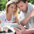 Couple sitting at a restaurant terrace with electronic tablet — Stock Photo