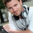Portrait of guy with music headphones sitting in town — Stock Photo