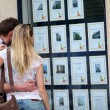 Couple looking at house-for-sale ads through shop window — Stock Photo #13942044