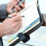 Closeup of businessman hand writing on agenda — Stock Photo #13942066