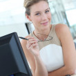 Beautiful businesswoman with eyeglasses sitting in office — Stock Photo