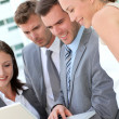 Stock Photo: Business team consulting program on laptop