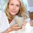Mature blond woman in couch having a tea — Stock Photo #13942608