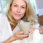 Olgun sarışın kadın kanepe bir çay içiyor — Stok fotoğraf #13942608