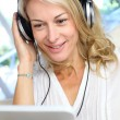 Middle-aged blond woman listening to music with tablet — Stock Photo #13942614