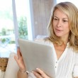 Beautiful mature woman using electronic tablet at home — Stock Photo #13942621