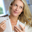 Middle-aged woman talking on mobile phone with handfree device — Stock Photo