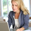 Middle aged blond woman working at home with laptop — Stock Photo #13942633