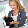 Woman photographer working from home on laptop — Stock Photo #13942639