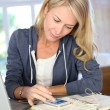 Middle-aged blond woman working at home with laptop — Stock Photo