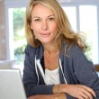 Royalty-Free Stock Photo: Middle-aged blond woman working at home with laptop