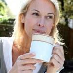 茶マグカップ外に座っている金髪の女性の肖像画 — ストック写真