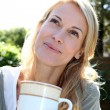 Portrait of blond woman with tea mug sitting outside — 图库照片