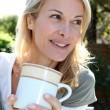 图库照片: Portrait of blond woman with tea mug sitting outside