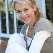 Portrait of smiling mature woman relaxing outside — Stock Photo #13942712