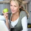 Cheerful adult woman websurfing with tablet and eating apple — Stock Photo