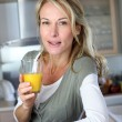 Portrait of blond woman in kitchen drinking orange juice — Stock Photo