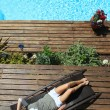 Stock Photo: Womrelaxing in deck chair by swimming pool