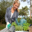 Woman in garden ready to water fresh plants - Stock Photo