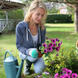 Cheerful blond woman planting flowers in garden — Stock Photo