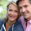 Stock Photo: Portrait of middle aged couple sitting outside the house