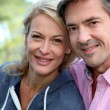 Portrait of middle aged couple sitting outside the house — Stock Photo
