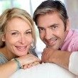 Middle aged couple relaxing in sofa at home — Stock Photo #13942950