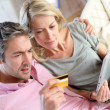 Couple sitting in sofa with electronic tablet -  