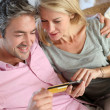 Upper view of couple paying with credit card on mobile phone — Stock Photo