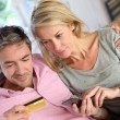 Stockfoto: Upper view of couple paying with credit card on mobile phone