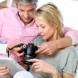 Couple at home looking at pictures on electronic tablet — Stockfoto