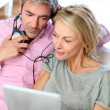 Couple listening to music at home with tablet — Stock Photo #13943106