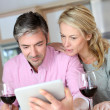 Couple in kitchen with glass of wine websurfing on tablet - Zdjęcie stockowe