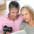 Couple at home looking at pictures on electronic tablet — Stok fotoğraf