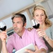 Stock Photo: Couple in kitchen with glass of wine websurfing on tablet