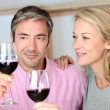 Couple drinking red wine in kitchen — Stock Photo
