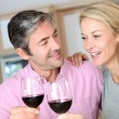 Happy couple in kitchen drinking red wine — Stock Photo #13943151